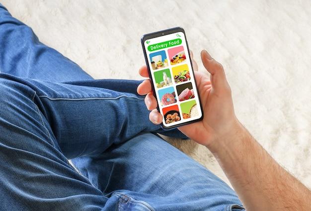 Uomo in jeans sdraiato sul divano e in possesso di telefono con cibo di consegna app sullo schermo. concetto di ordine alimentare.
