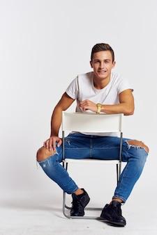 Un uomo in jeans si siede su una sedia all'indietro e jeans strappati vista frontale della maglietta.