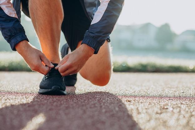 Uomo che fa jogging allaccia i lacci delle scarpe allo stadio