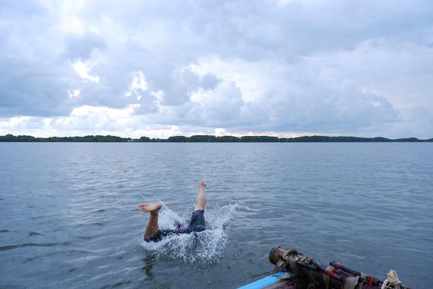 Un uomo salta da una casa galleggiante in mare con una strana postura.