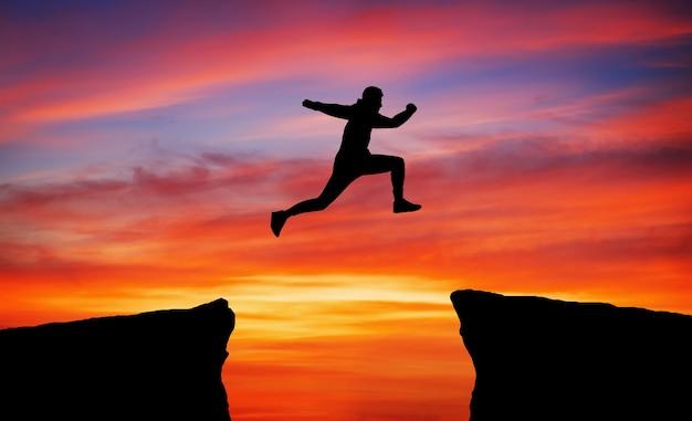 L'uomo salta attraverso il divario da una roccia per aggrapparsi all'altra. l'uomo che salta sopra le rocce con gap su sfondo infuocato tramonto. elemento di design.