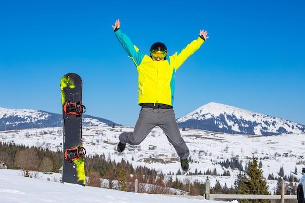 L'uomo che salta vicino al bastone da snowboard nelle montagne di neve sullo sfondo. giorno soleggiato. divertirsi