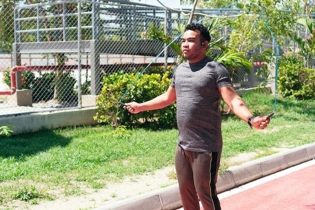 Uomo che salta la corda nel parco al mattino. concetto di stile di vita sano