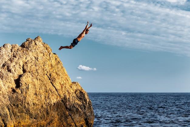 Un uomo si butta in mare da un'alta scogliera