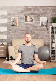 Uomo che tiene gli occhi chiusi facendo yoga a casa durante il blocco del covid-19.
