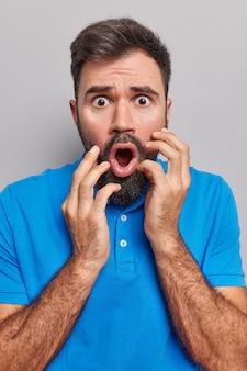L'uomo tiene la bocca aperta occhi schioccanti reagisce stupito sente notizie inquietanti indossa una maglietta blu casual guarda eccitato isolato su grigio