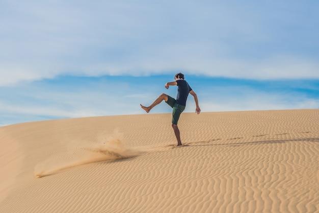 L'uomo calcia la sabbia, fastidio, aggressione nel deserto del vietnam