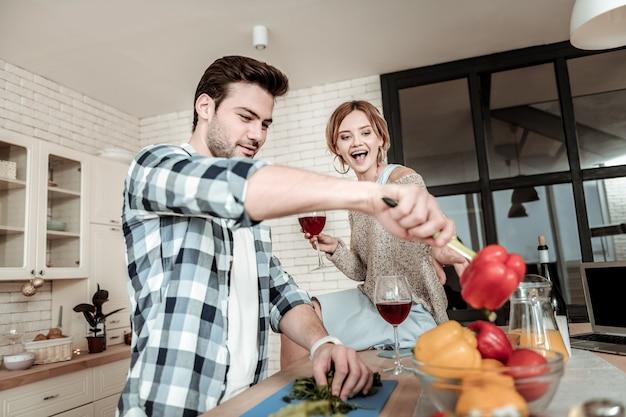 Uomo in cucina. bell'uomo dai capelli scuri che indossa una camicia a scacchi divertendosi con le verdure