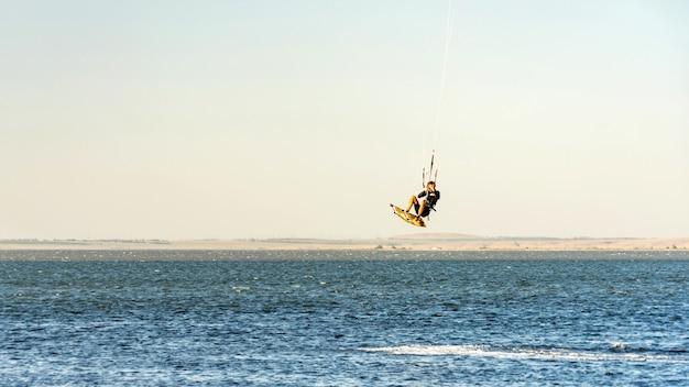 L'uomo kitesurfer guida il salto con gli aquiloni. costa del mar nero in giornata di sole. blagoveshenskaja. anapa, russia.
