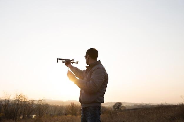 Un uomo lancia un drone nel cielo. operatore di drone con sole al tramonto.