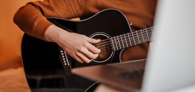 Uomo che impara a suonare la chitarra con l'aiuto dell'apprendimento online a casa. ragazzo seduto al tavolo con laptop e chitarra nera