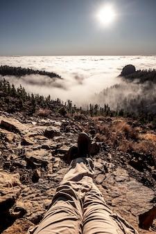 Punto di vista delle gambe dell'uomo con il trekking di persone attive che riposano sulle rocce e si godono il bellissimo panorama selvaggio con montagne e foreste sulle nuvole e il cielo in backgorund