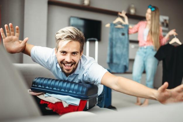 L'uomo giace su una valigia troppo piena, le tasse sul viaggio