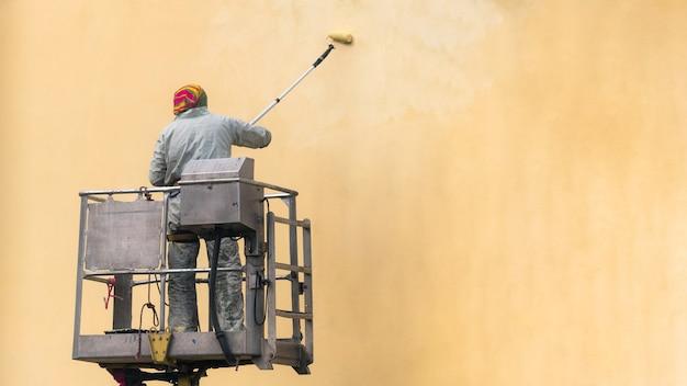 Uomo su una piattaforma elevatrice che dipinge la parete dell'edificio con un rullo esterno all'esterno.