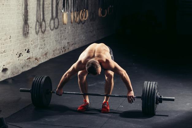 Uomo sollevamento pesi. allenamento uomo muscoloso in palestra facendo esercizi con bilanciere