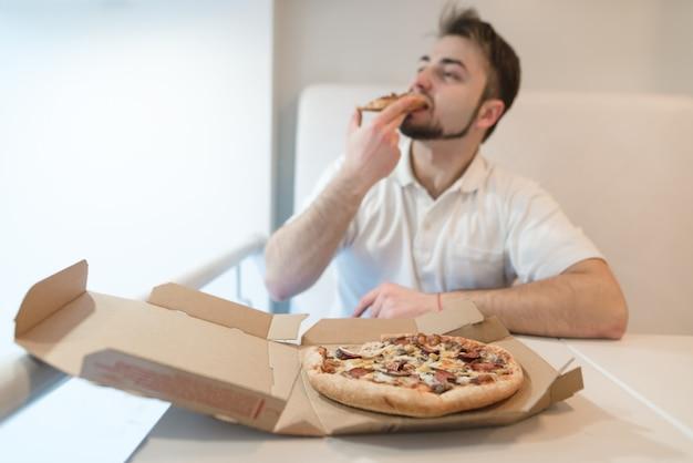 Un uomo in abiti leggeri mangia una deliziosa pizza da una scatola di cartone. focus sulla scatola di cartone con la pizza.