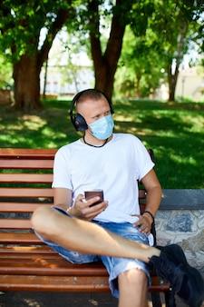 Uomo che ascolta musica con le cuffie, utilizza lo smartphone che indossa la maschera protettiva per il viso all'aperto nel parco, stile di vita nuovo normale