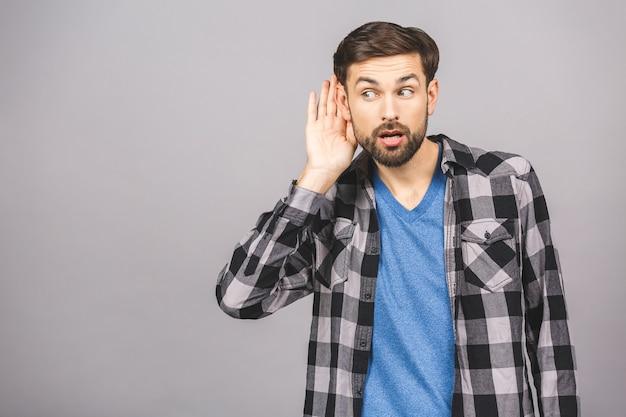 L'uomo ascolta attentamente con il palmo della mano l'orecchio su un muro bianco grigio grigio, il concetto di notizie, lo spazio della copia.