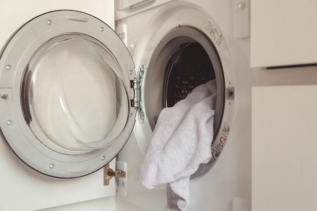 Uomo che carica i vestiti e gli asciugamani di colore nella lavatrice incorporata