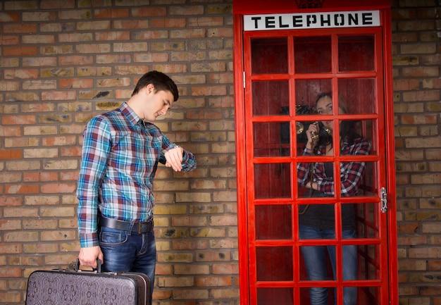 Uomo che guarda il suo orologio da polso per controllare l'ora mentre tiene in mano una valigia accanto a una cabina telefonica rossa con la sua ragazza all'interno che chiacchiera al telefono