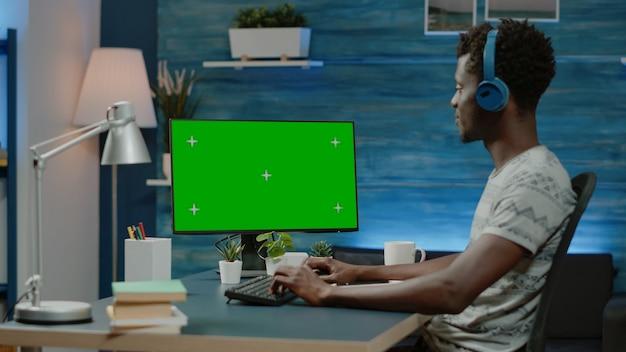 Uomo che guarda lo schermo verde orizzontale sul computer per il lavoro a distanza