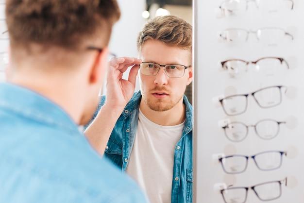 Uomo che cerca nuovi occhiali all'optometrista