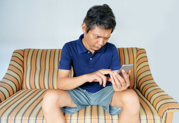Uomo che guarda lo schermo del telefono sul divano
