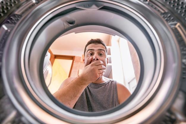 Uomo che esamina il panno candeggiato macchiato in lavatrice