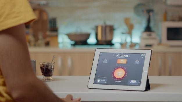 Uomo che guarda un tablet con software di automazione dell'illuminazione wireless posizionato sulla scrivania della cucina, casa con sistema intelligente, accensione delle luci. tablet digitale con app ad alta tecnologia per il controllo dell'efficienza elettrica