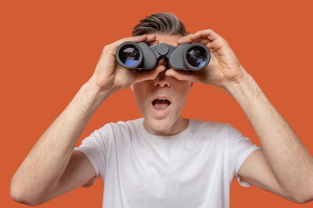 Uomo che guarda attraverso il binocolo con la bocca aperta