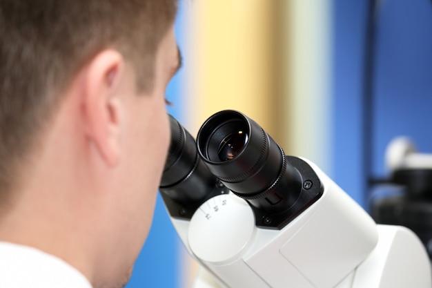 Uomo che guarda attraverso un primo piano del microscopio