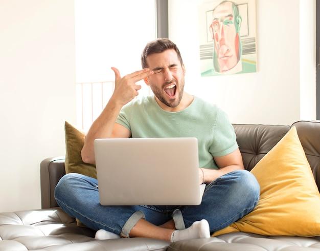 Uomo che sembra infelice e stressato, gesto suicida che fa il segno della pistola con la mano, indicando la testa