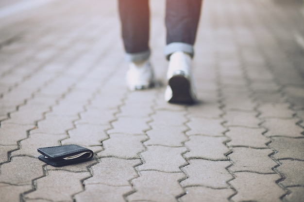 Uomo in cerca di portafoglio posa sul marciapiede