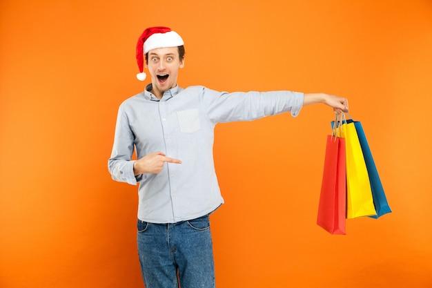 Uomo che guarda con la faccia sorpresa uomo scioccato che tiene in mano molte borse colorate e punta il dito su di esse