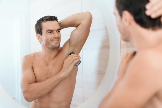 L'uomo guarda ascella specchio e deodorante bagno.
