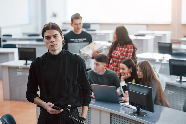 L'uomo sembra dritto. gruppo di giovani in abiti casual che lavorano nell'ufficio moderno.