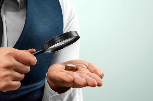 Un uomo guarda attraverso una lente d'ingrandimento una pila di monete nel suo palmo. piccolo stipendio, fallimento.