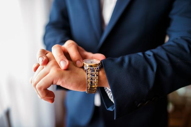 Un uomo guarda a che ora sui loro orologi