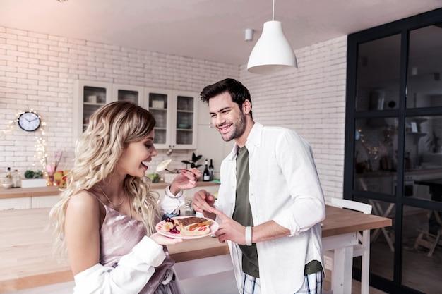 Uomo innamorato. uomo barbuto dai capelli scuri in una camicia bianca guardando sua moglie mentre si trovava in cucina