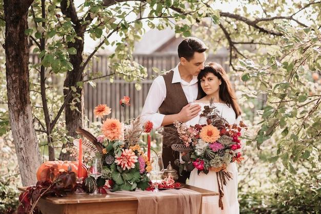 Un uomo innamorato abbraccia una ragazza con un bouquet di erbe e fiori tra le mani.