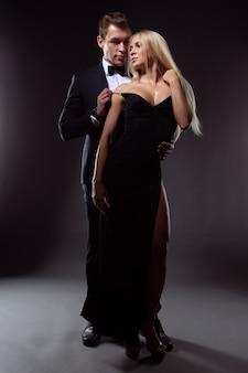 Un uomo innamorato in un vestito abbraccia delicatamente una giovane donna bionda sexy in un abito da sera