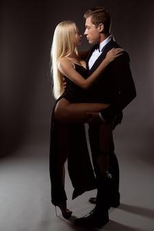 Un uomo innamorato in un abito abbraccia dolcemente la sua amata donna aggrappata a lui in un abito da sera sexy.