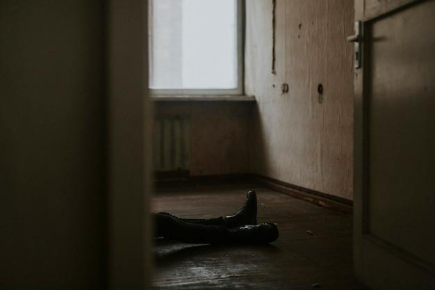 Uomo disteso sul pavimento di un appartamento vuoto