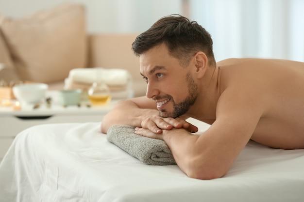 Uomo disteso sul lettino da massaggio nel salone della stazione termale