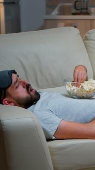 Uomo sdraiato sul divano che mangia popcron e guarda la tv