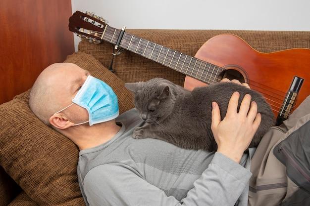 Uomo sdraiato su un divano con un gatto durante la quarantena dell'infezione da coronavirus in una maschera medica