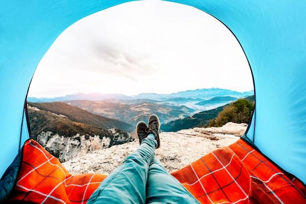 Uomo disteso in una tenda con vista sulle montagne e sul tramonto