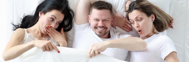 Uomo sdraiato con due amanti a letto, donne che guardano sotto copertura e si chiedono sesso promiscuo