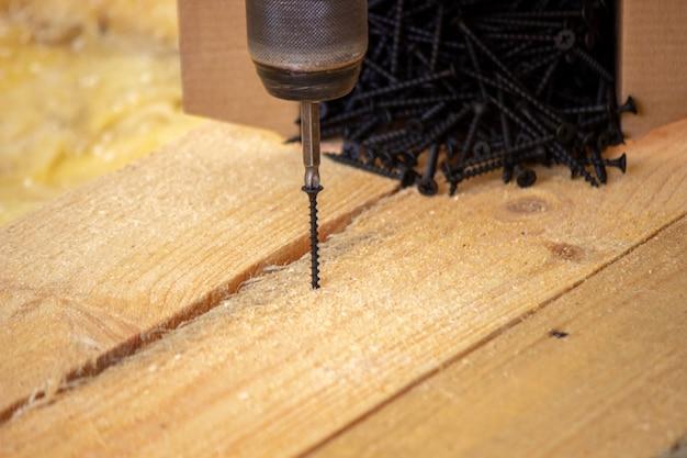 Un uomo fa le riparazioni in casa, un cacciavite, delle viti, una sega. pavimento di legno. messa a fuoco selettiva