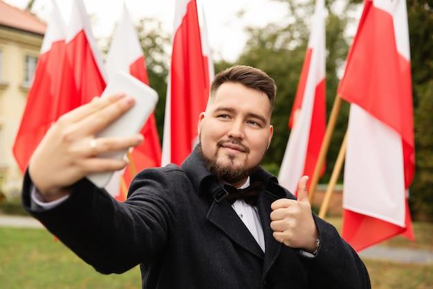 L'uomo fa selfie con le bandiere della polonia dietro